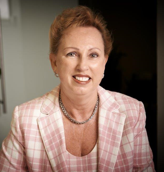 Margaret Scott is smiling. She has red hair and is wearing a pink and white checkered suit.