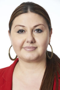 Francesca is smiling at the camera. Her hair is pulled back and she is wearing large hoop earrings and a red blouse.